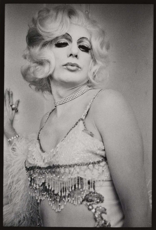 A black and white photograph of a drag queen dressed as Jean Harlow