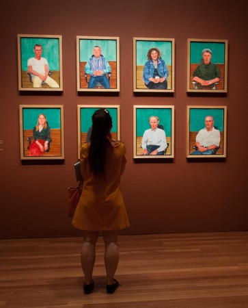 A woman stands before eight colorful portraits hung in two rows of four.