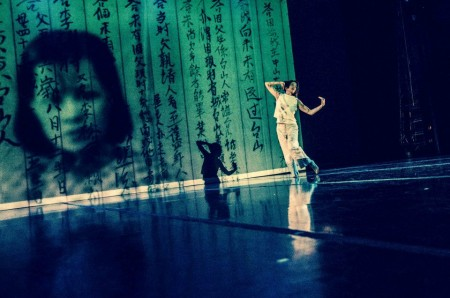 A dancer on stage infront of a scrim onto which is projected Chinese characters