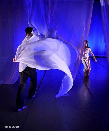 Two dancers move between flowing fabric in a blue tone