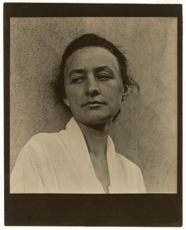 A black and white portrait of Georgia O'Keeffe leaning against an adobe wall