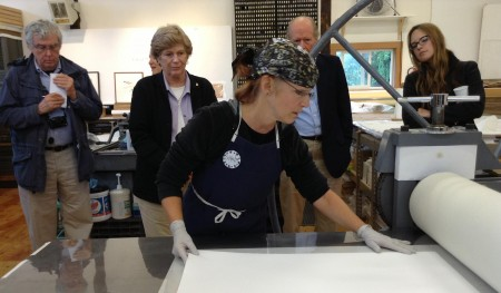 A master printer wearing a bandana rolls out a large-format piece of paper onto a printing table.
