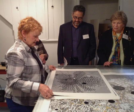 A print artist shows of a black and white work on paper to a group.
