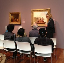 Docent in the galleries with seated guests.