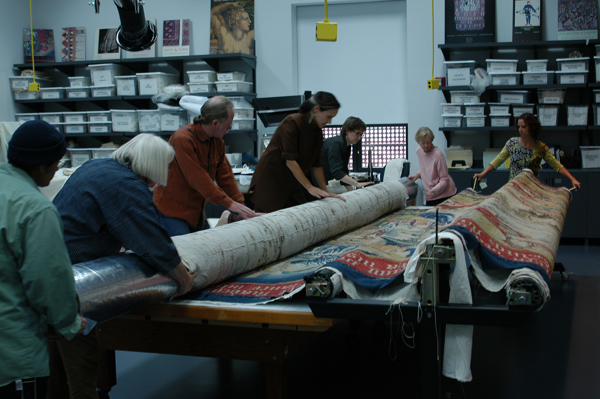 Seven staff members and volunteers work together to unfurl a monumental tapestry