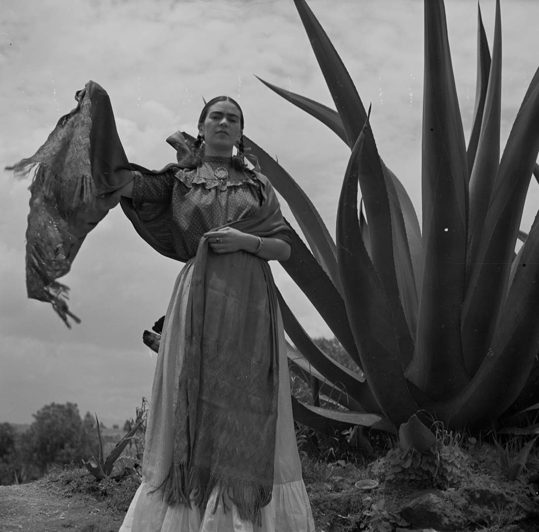 """Toni Frissell, Frida Kahlo (Senora Diego Rivera) standing next to an agave plant, during a photo shoot for Vogue magazine, """"Senoras of Mexico,"""" 1937 Negative, nitrate. Library of Congress, Washington, D.C. Library of Congress, Prints & Photographs Division, Toni Frissell Collection, LC-DIG-ds-05052"""