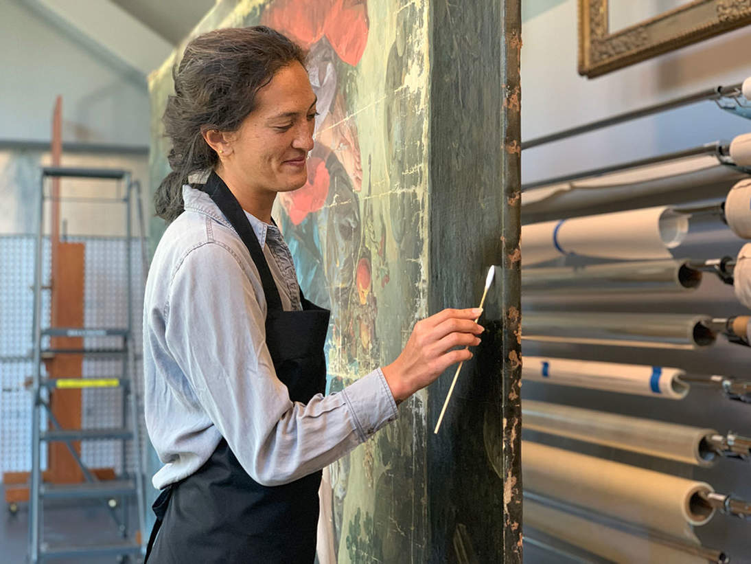 Kathryn Harada, Getty Conserving Canvas Fellow, cleaning the front of the painting