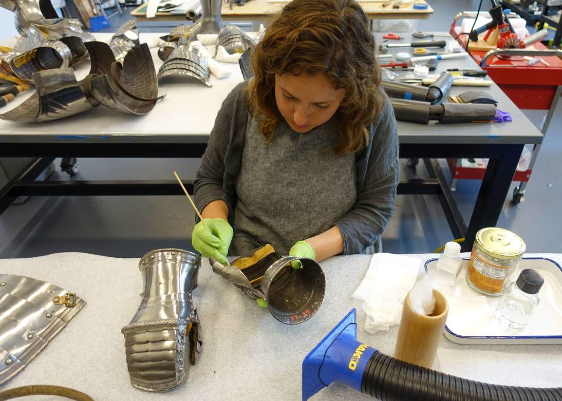 Assistant conservator Jena Hirschbein uses solvents to reduce fingerprints and light corrosion on the surfaces of the disassembled armor.