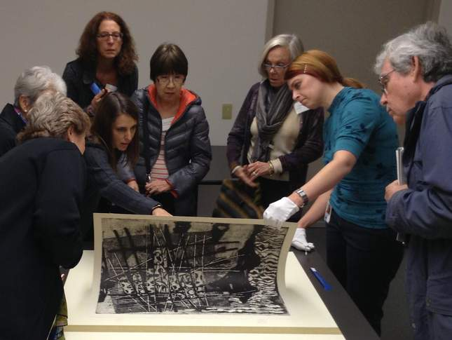 A group of people stand around a printed artwork being peeled off of a table.