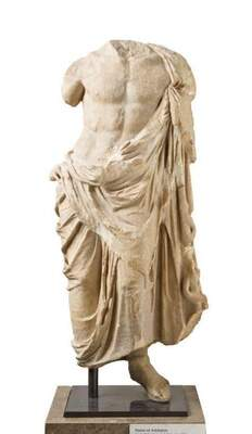 Image of a marble sculpture of a standing male body partially draped by a cloth from the left shoulder, tied at the waist and falling in folds to just above the ankle. The chest is bare and pectoral and abdominal muscles are exposed. The head, arms, and one foot are missing.